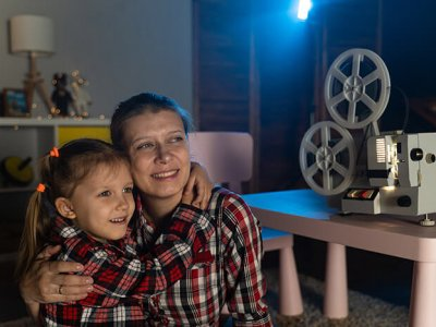 Mother and daughter watching old movie on retro vintage film projector at home
